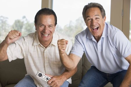 Two men in living room with remote control cheering and smiling Stock Photo - 3472452