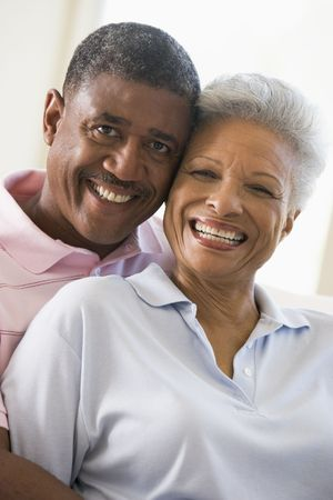 senior living: Couple relaxing in living room and smiling Stock Photo