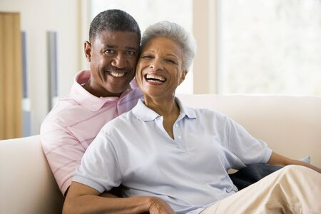 senior couples: Couple relaxing in living room and smiling Stock Photo