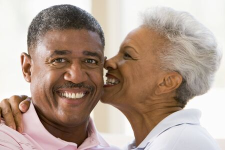 Couple relaxing indoors kissing and smiling Stock Photo - 3471572