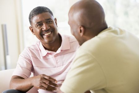 50s man: Two men in living room talking and smiling