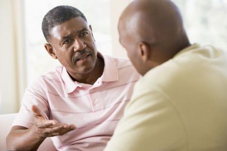 hombre sentado: Dos hombres en la sala hablando Foto de archivo