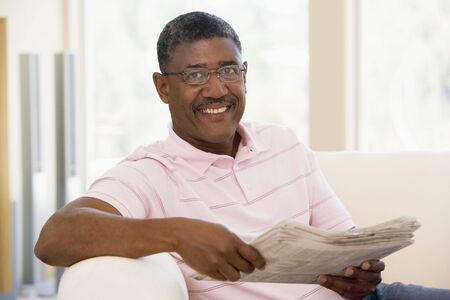 mature male: Man relaxing with a newspaper smiling Stock Photo
