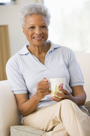 Woman sitting in living room with coffee smiling photo