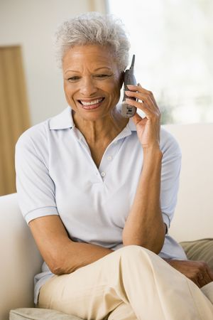 home phone: Woman sitting in living room using telephone and smiling Stock Photo