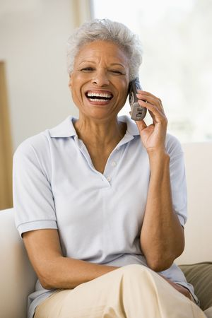 cordless phone: Woman sitting in living room using telephone and smiling Stock Photo