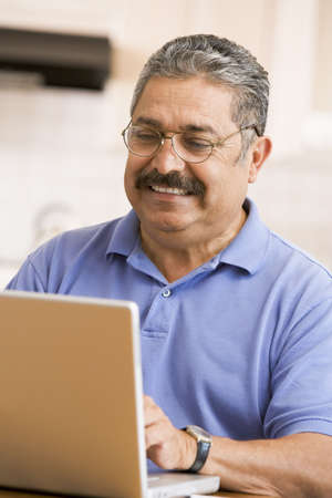 Man in kitchen with laptop smiling photo