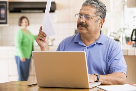 Man in kitchen with laptop and paperwork with woman in background photo