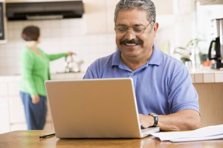 Man in kitchen with laptop smiling with woman in background photo