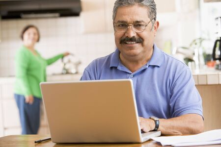 silver surfer: Man in kitchen with laptop smiling with woman in background