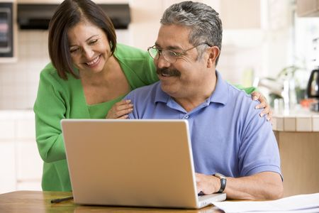 internet surfing: Couple in kitchen with laptop smiling Stock Photo