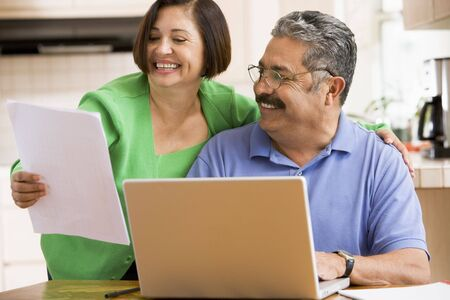 Couple in kitchen with laptop and paperwork smiling photo