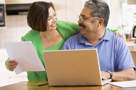 silver surfer: Couple in kitchen with laptop and paperwork smiling Stock Photo