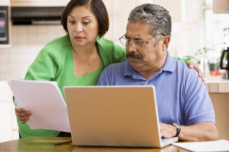 couple fach�: Couple dans la cuisine avec un ordinateur portable et de la paperasserie