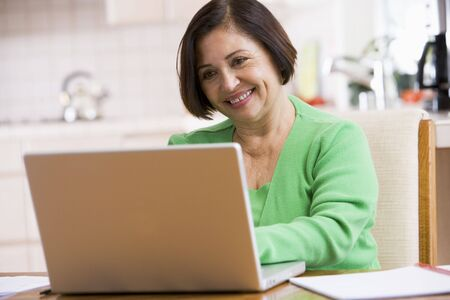 silver surfer: Woman in kitchen with laptop smiling