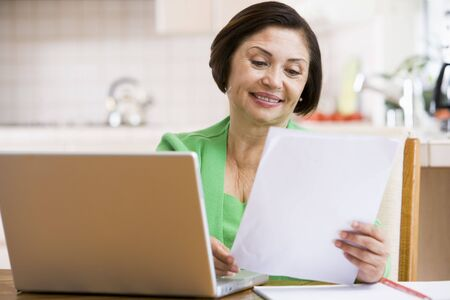 woman with document: Woman in kitchen with laptop and paperwork smiling Stock Photo