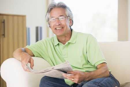 Man relaxing with a newspaper smiling photo