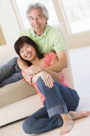 Couple relaxing in living room and smiling Stock Photo - 3472716