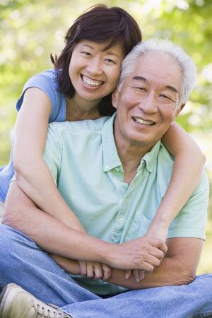 Couple relaxing outdoors in park smiling photo