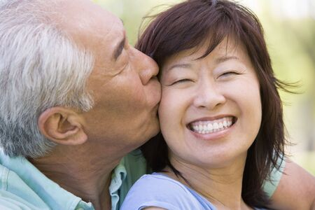 Couple relaxing outdoors in park kissing and smiling photo