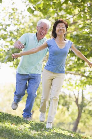 Couple running outdoors in park by lake smiling photo