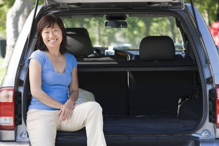 Woman sitting in back of van smiling photo