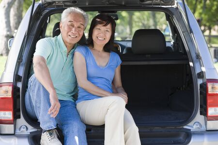 Couple sitting in back of van smiling photo