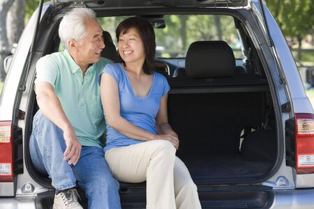 mpv: Couple sitting in back of van smiling