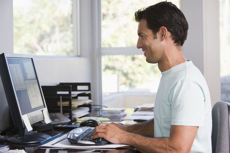 Man in home office using computer and smiling Stock Photo - 3460998