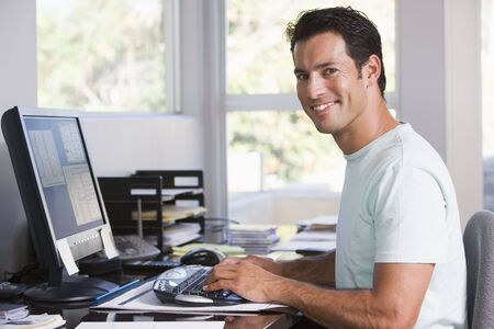 Man in home office using computer and smiling Stock Photo - 3461073