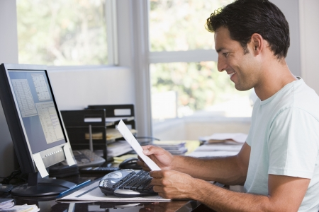 home office desk: Man in home office using computer holding paperwork and smiling