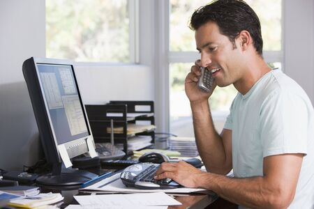 Man in home office on telephone using computer and smiling Stock Photo - 3461072