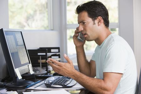 home phone: Man in home office on telephone using computer and frowning
