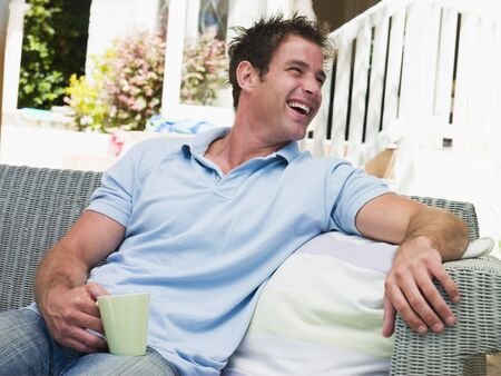 Man sitting on patio with coffee laughing photo
