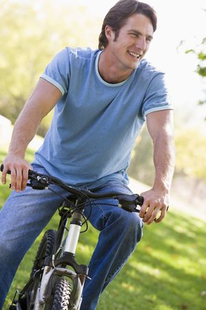 Man outdoors on bike smiling photo