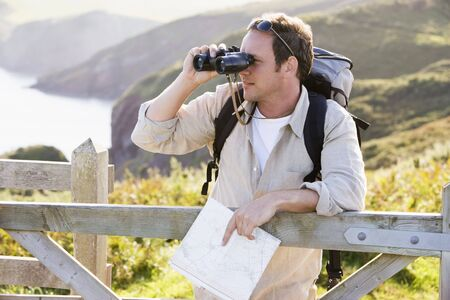 rambling: Man relaxing on cliffside path holding map and binoculars