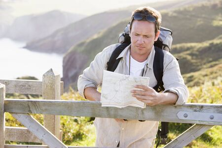 Man relaxing on cliffside path holding map photo