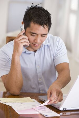 pay desk: Man in dining room on cellular phone using laptop