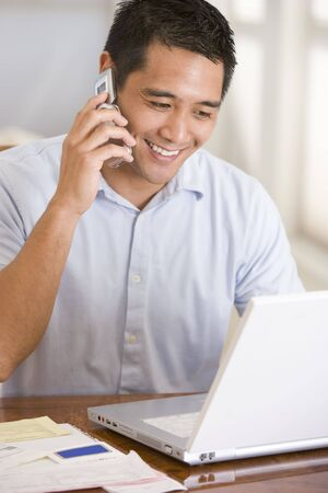 mobile phone adult: Man in dining room on cellular phone using laptop smiling