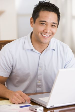 pay desk: Man in dining room using laptop smiling Stock Photo