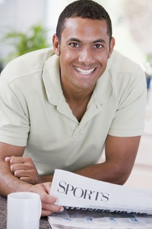 Man in kitchen reading newspaper and smiling photo