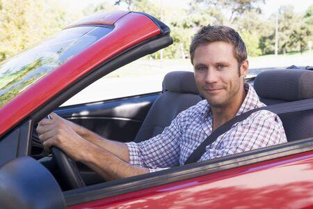 convertible car: Man in convertible car smiling Stock Photo