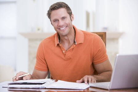 Man in dining room with laptop smiling photo