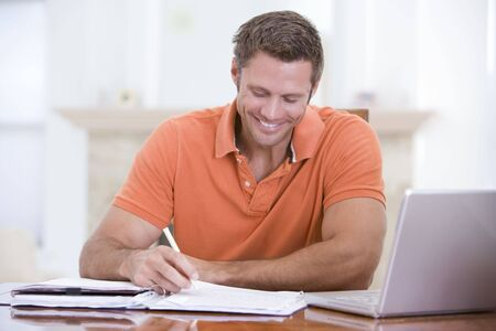 Man in dining room with laptop writing and smiling photo