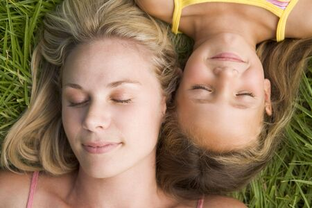 Woman and young girl lying in grass sleeping photo