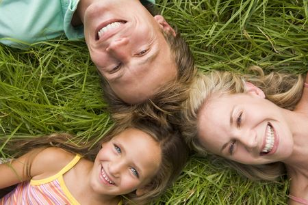 Family lying in grass smiling photo