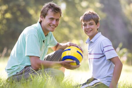 Man and young boy outdoors with soccer ball smiling photo