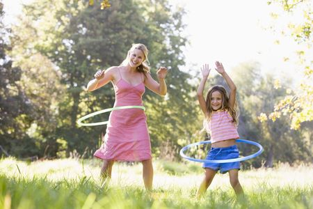 Woman and young girl with hula hoops outdoors smiling photo