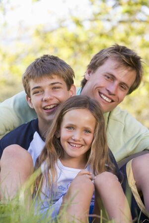 Man with two children sitting outdoors smiling Stock Photo - 3461255