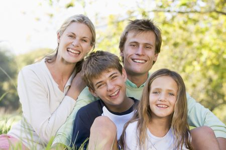 Family sitting outdoors smiling Stock Photo - 3460842